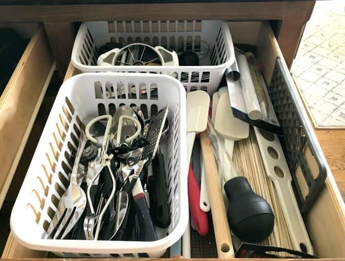 Efficient kitchen organization ideas; Organizing similar sized items together in bins in kitchen drawers to maximize space.