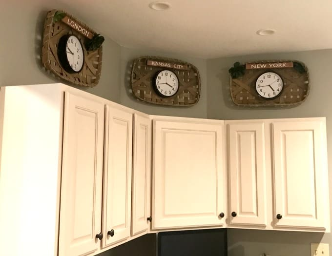 Time zone clocks wall displaying times for London, Kansas City and New York for above cabinet wall decor.