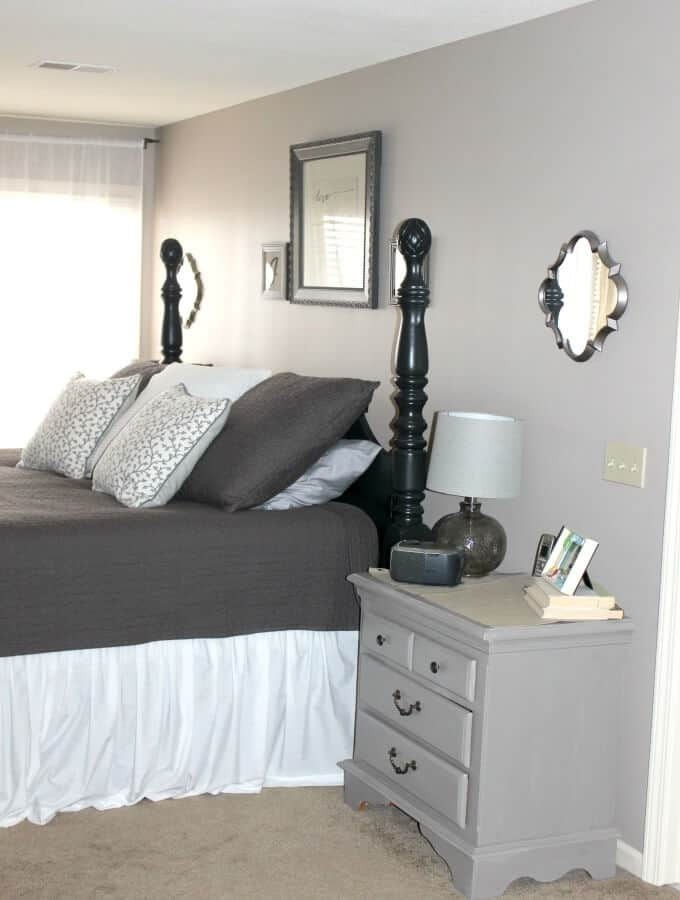 Tips to keep a clean bedroom; gray and white bedspread with gray painted nightstand.