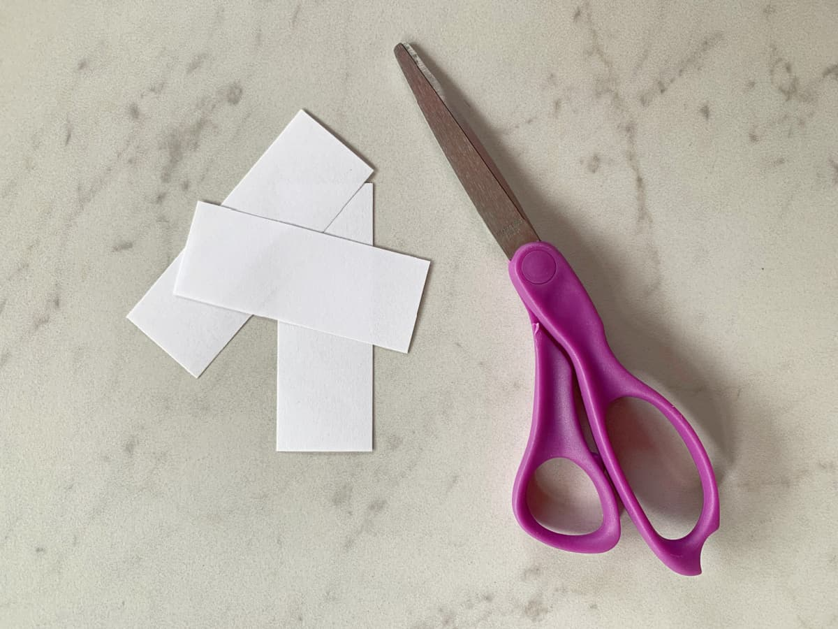 small strips of white paper with purple scissors