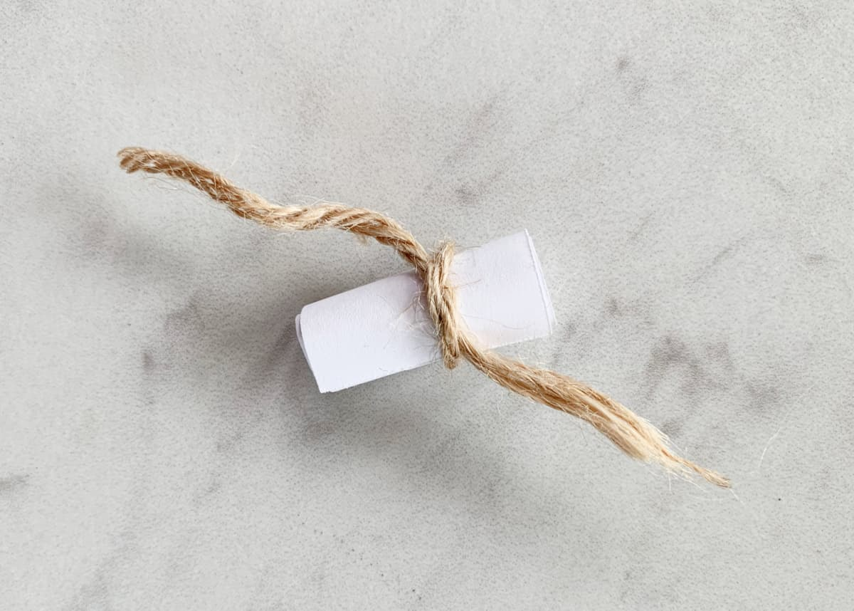 small white paper rolled into scroll and tied with twine