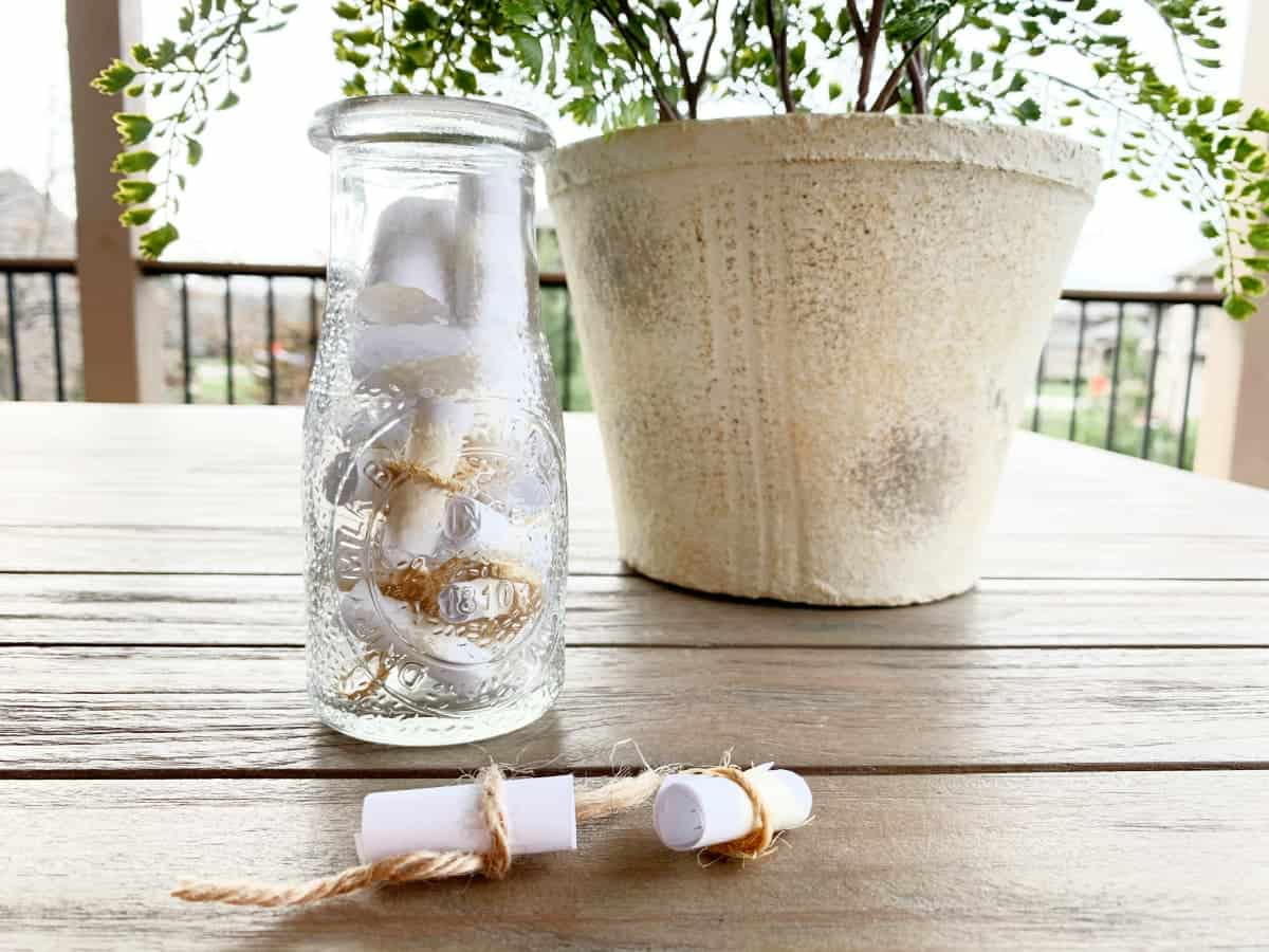 scrolls in clear vase by plant
