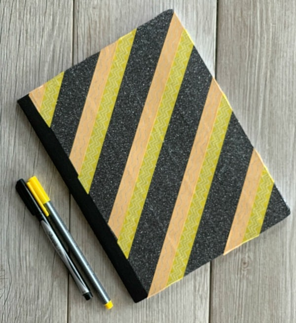 Notebook covered in yellow, gold, and black washi tape