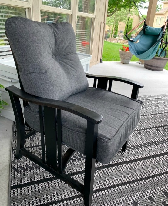 Gray patio cushions in black metal outdoor chair after spray paint