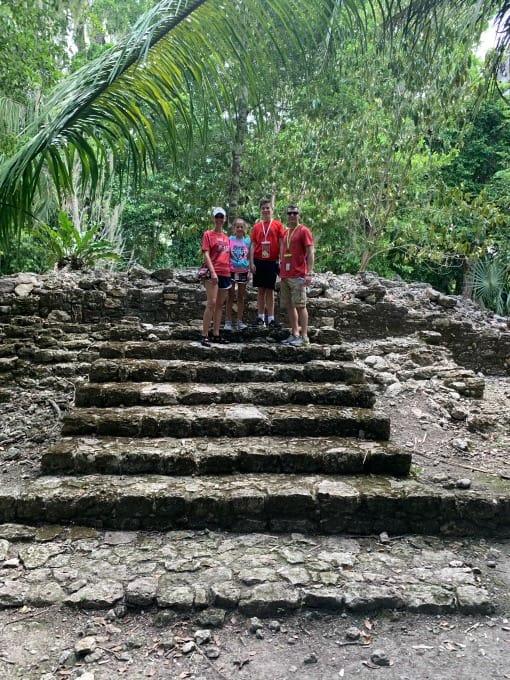 Climbing stairs at Chacchoben Ruins
