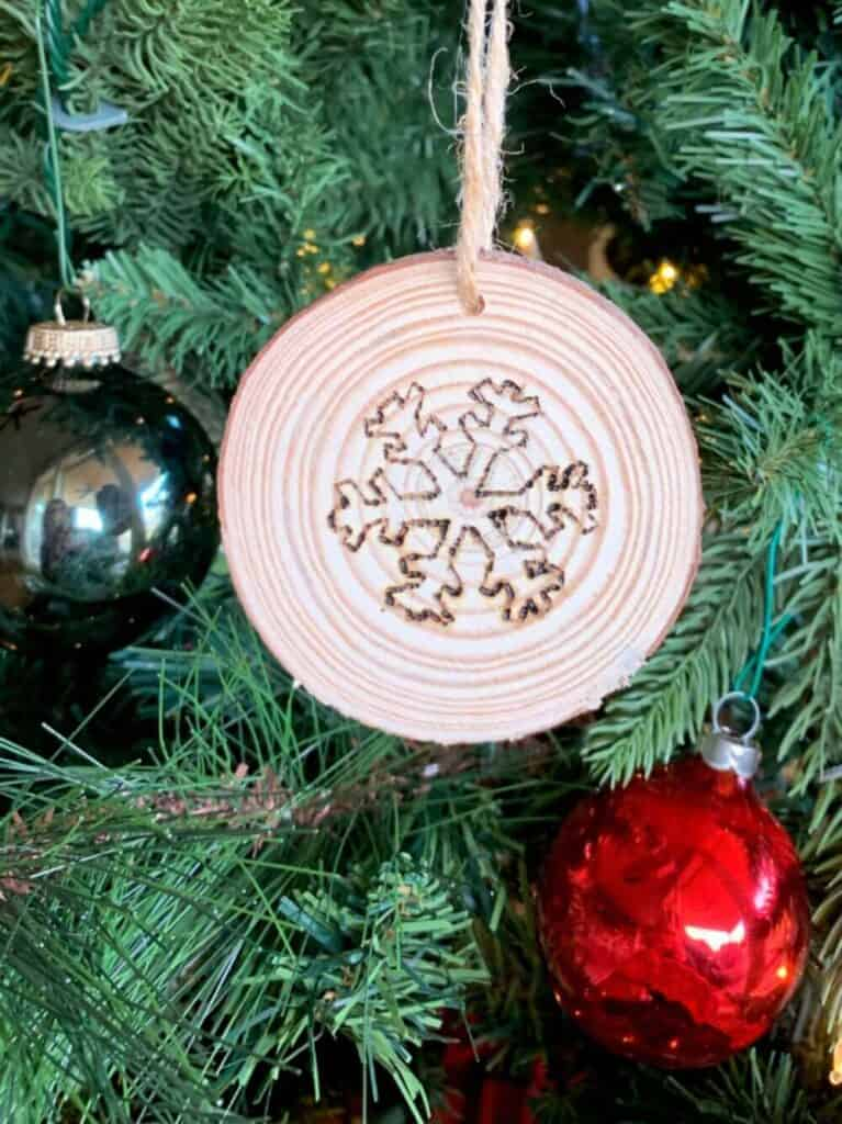 diy snowflake christmas ornament on wood slice