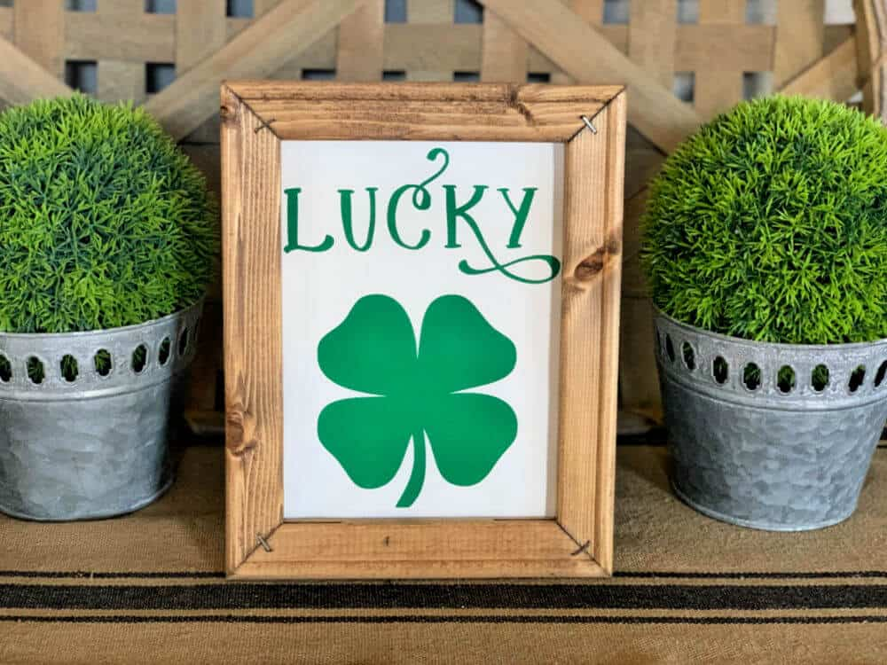 diy lucky st patricks day reverse canvas sign with stained wood frame with green topiary balls in background