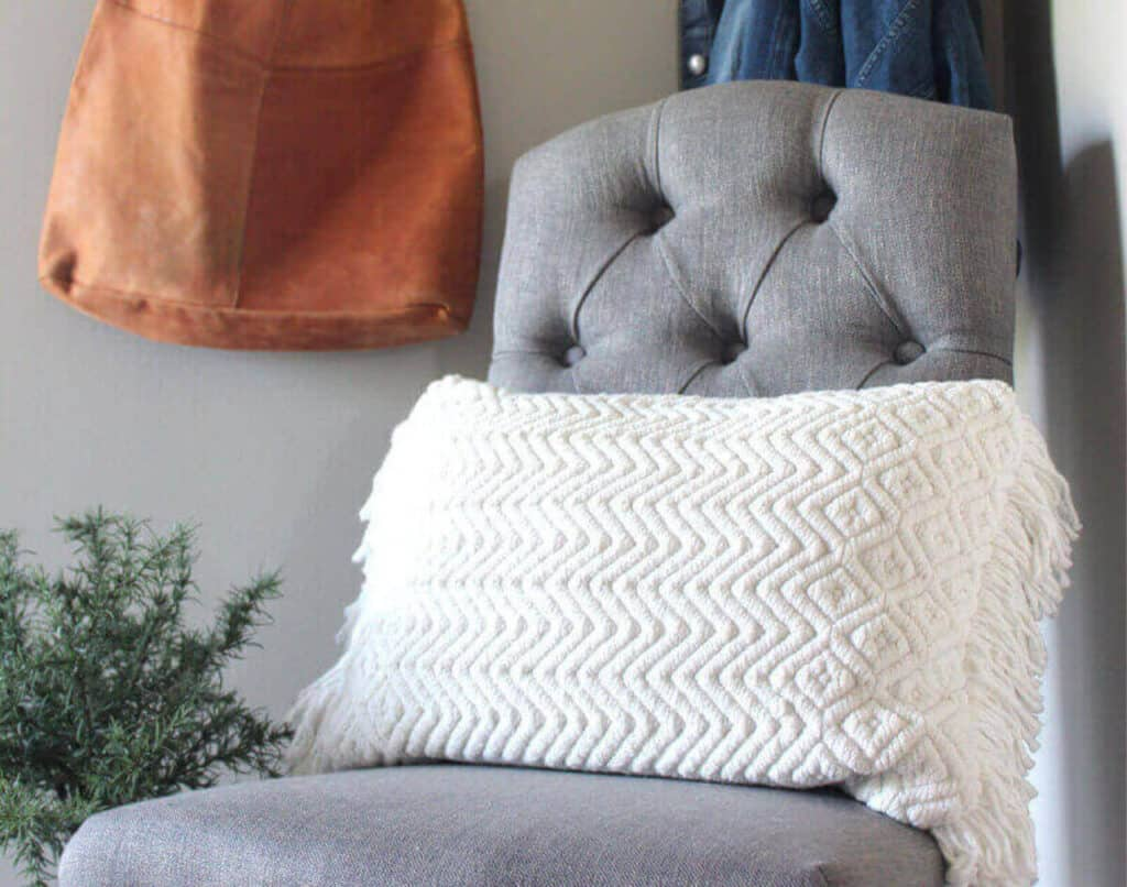 Gray chair with cream pillow in entry