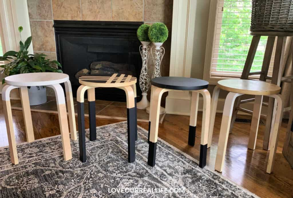four bar stools that have been painted black or white