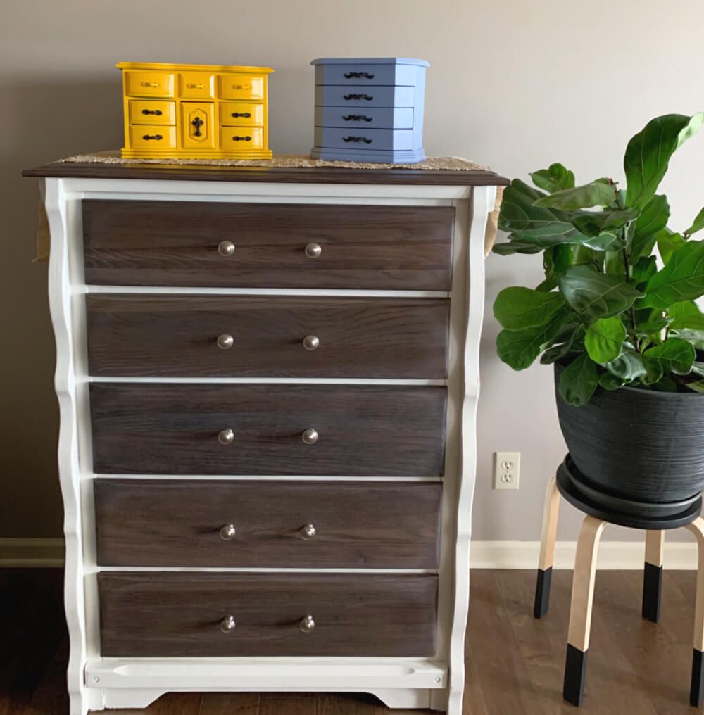 Painted and stained chest of drawers with yellow and periwinkle blue jewelry box with fiddle leaf fig plant beside it.