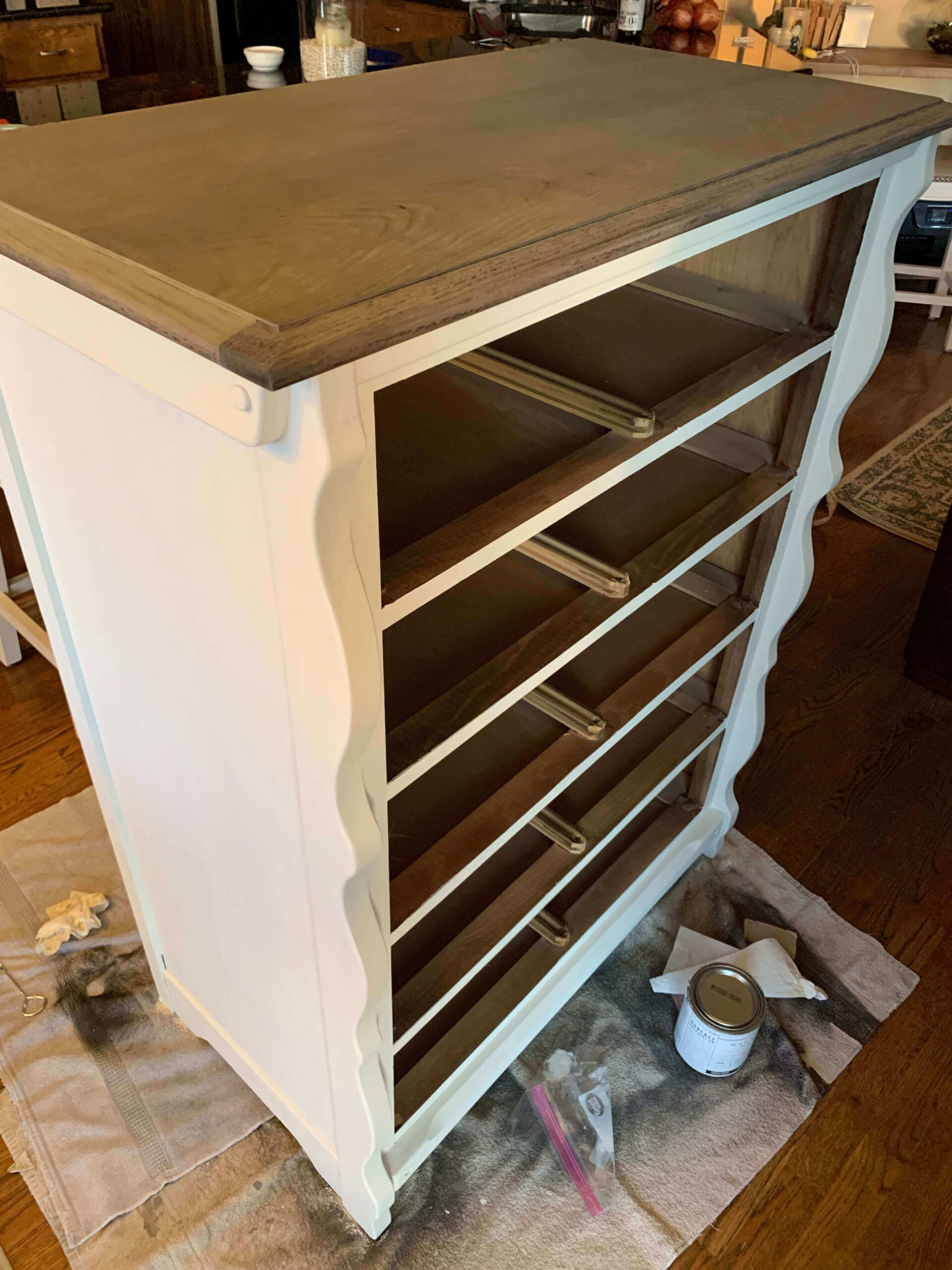 White chest of drawer with wood stained top.