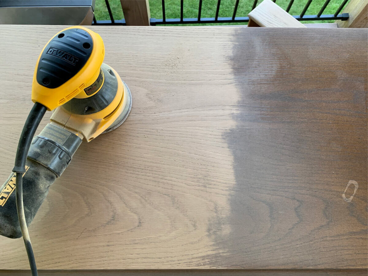 Removing stain from wood with sander.