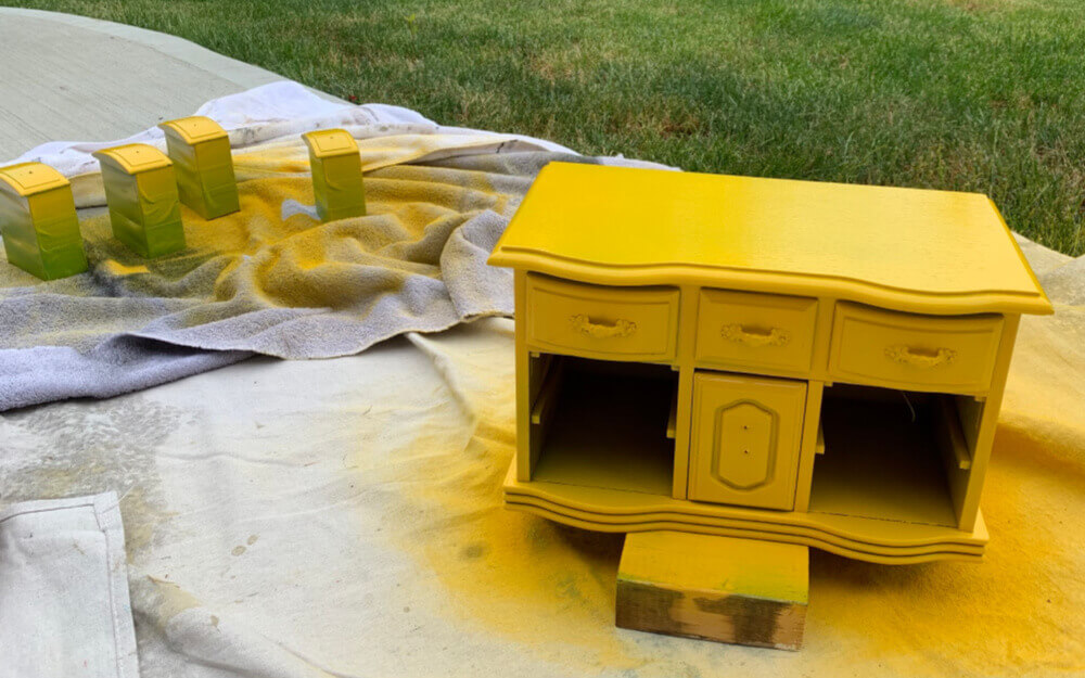 Using yellow paint on jewelry box sitting on drop sheet.