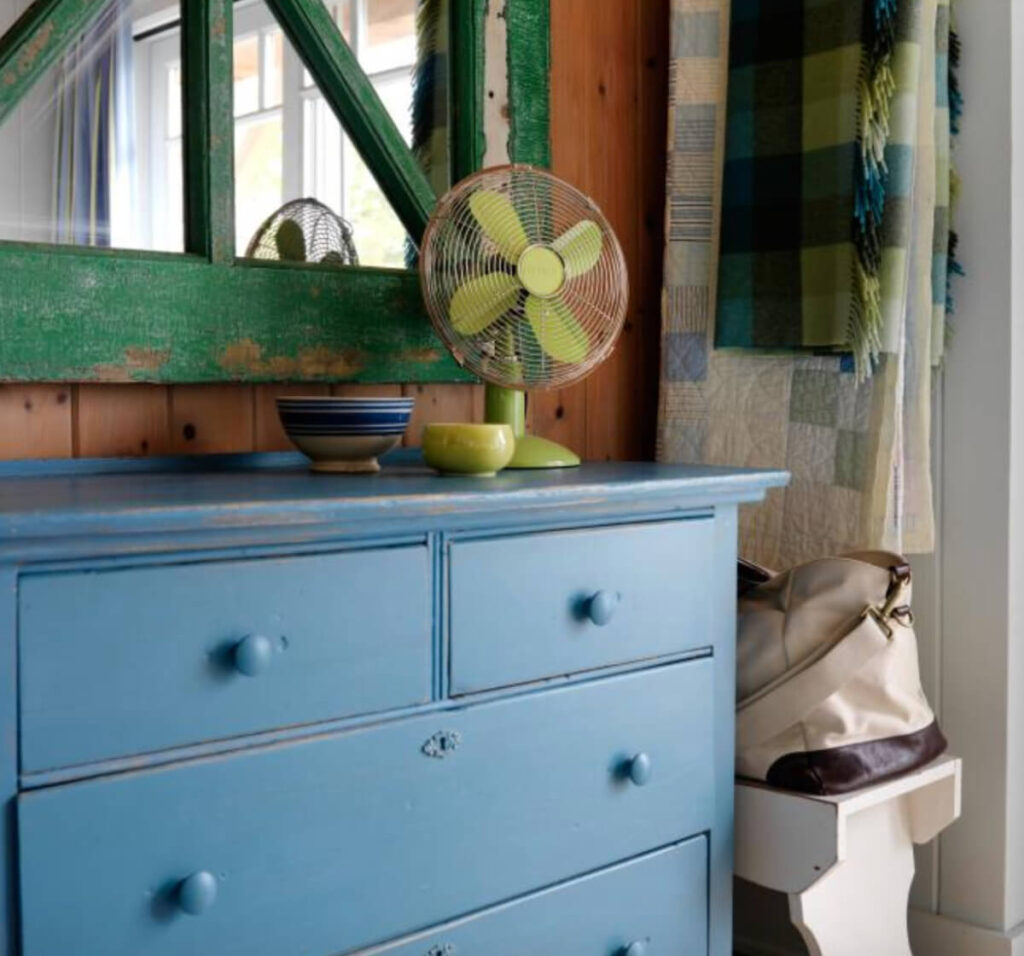 farmhouse style blue dreseer with vintage green mirror