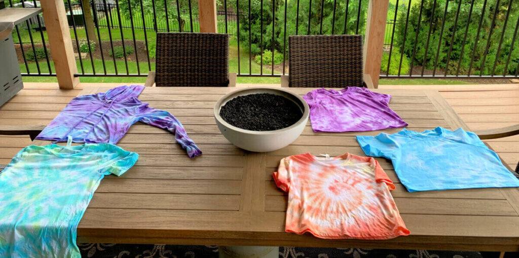 5 different tie dye shirt colors laying on a table