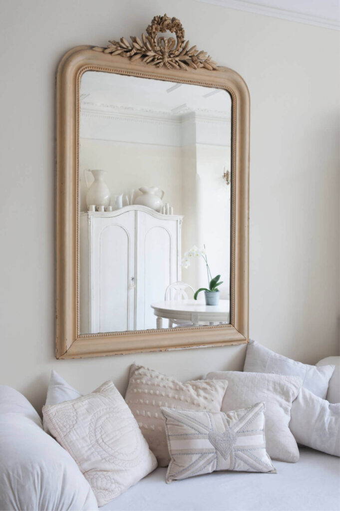 gold mirror with white armoire in background