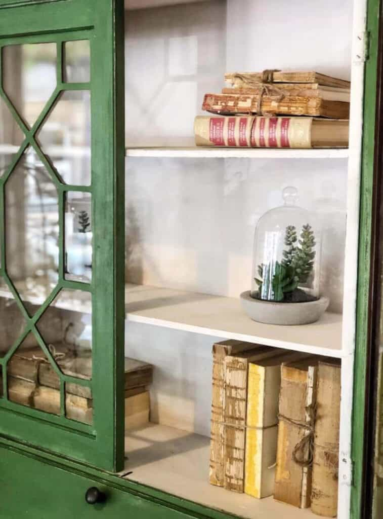 green armoire with decorated with old books