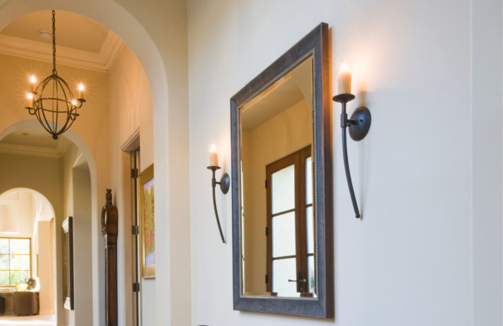 large wall mirror with candle sconces flanking mirror