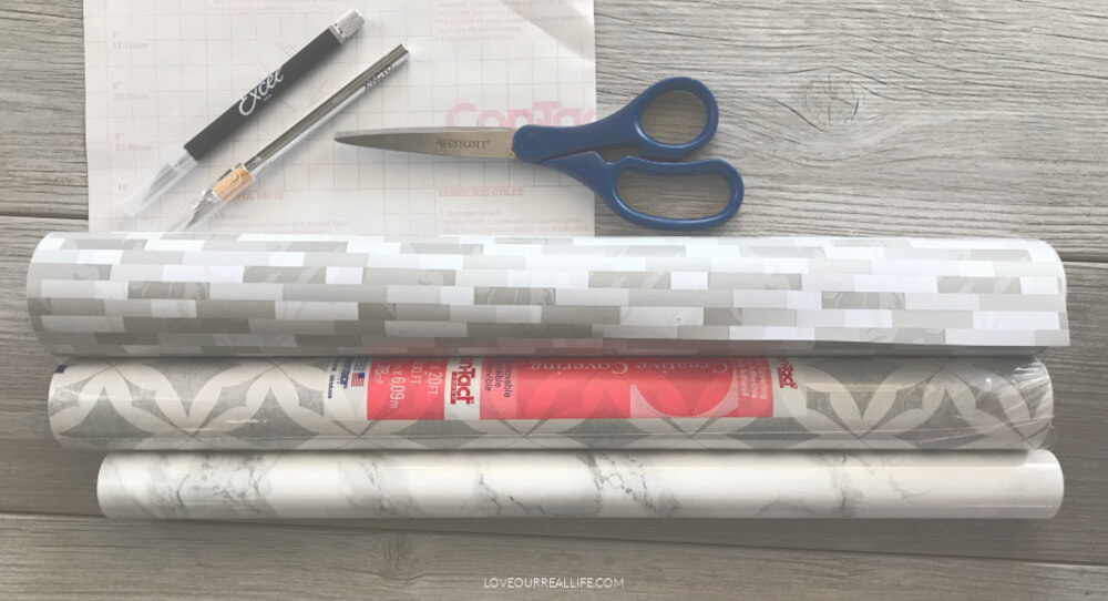 3 gray and white patterned contact paper rolls with Xacto knife and scissors