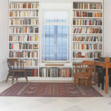 ceiling height bookshelves wrapped around window