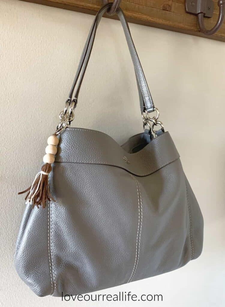 gray Coach purse with bead and tassel keyring