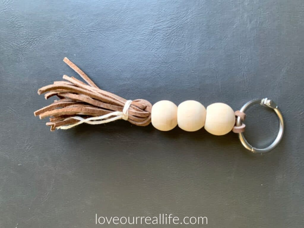 three natural wood beads on keychain with leather tassel in brown