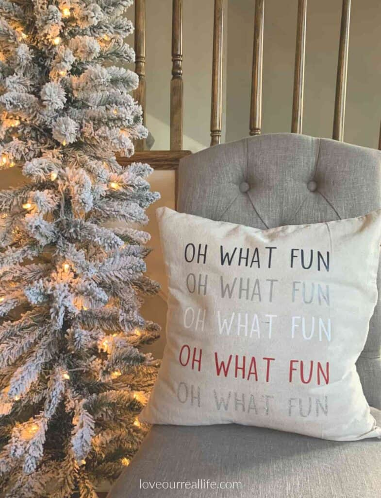 flocked christmas tree and christmas pillow on gray chair