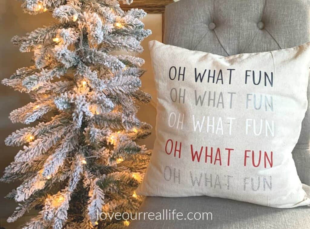 Oh what fun Christmas pillow sitting on gray dining chair by flocked tree.