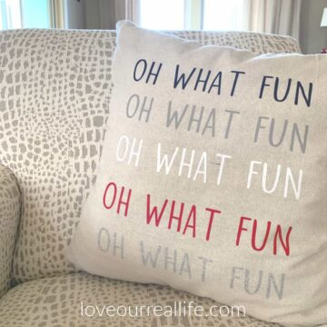oh what fun pillow on cream and gray chair