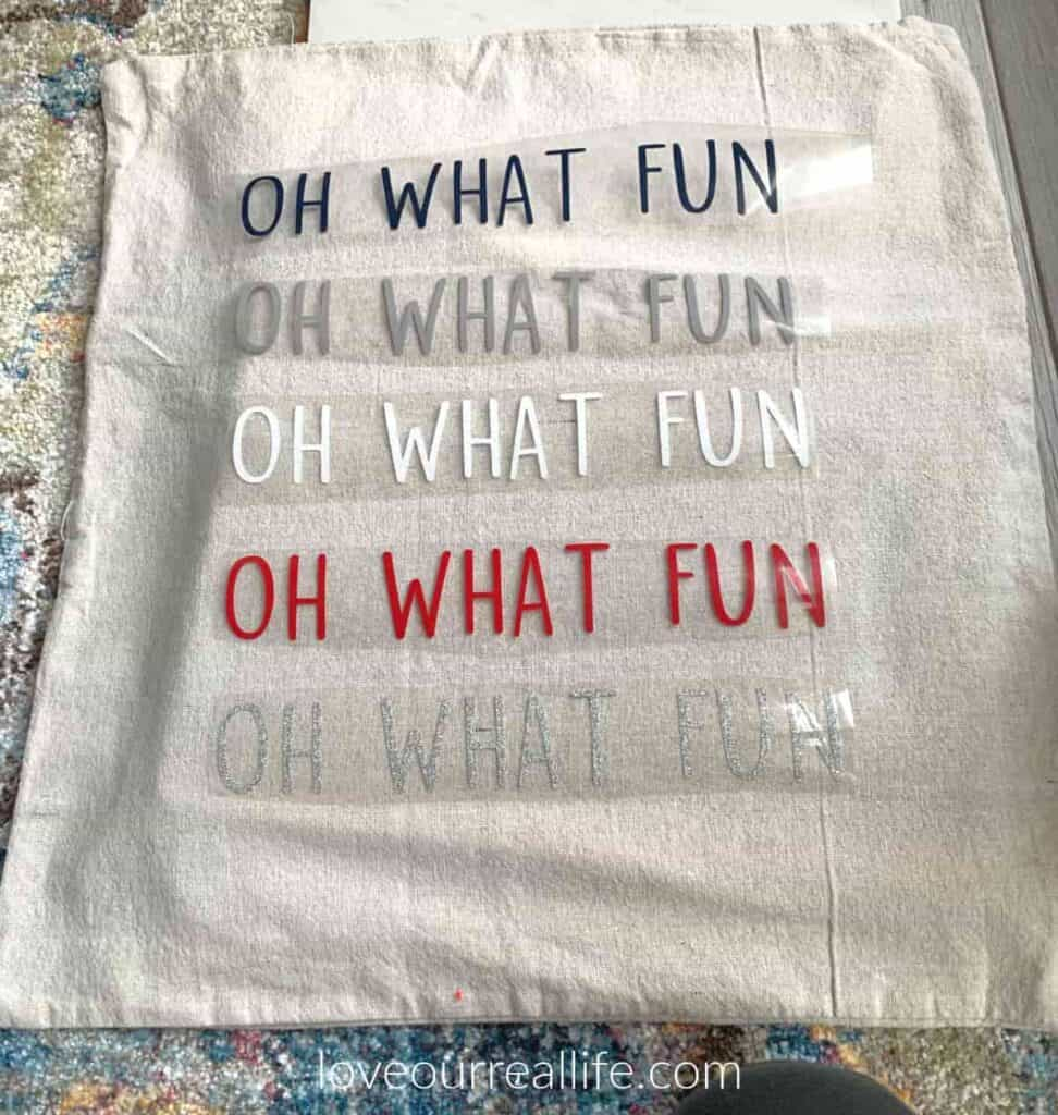 placing vinyl on pillow cover prior to ironing 'oh what fun' in various colors