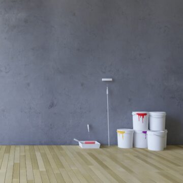Several 5 gallon buckets of paint beside paint roller and paint tray in gray room