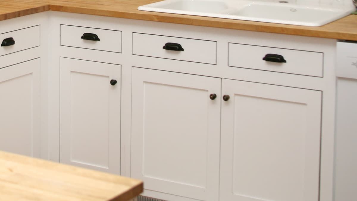 white cabinet with black drawer pulls and butcher block countertops