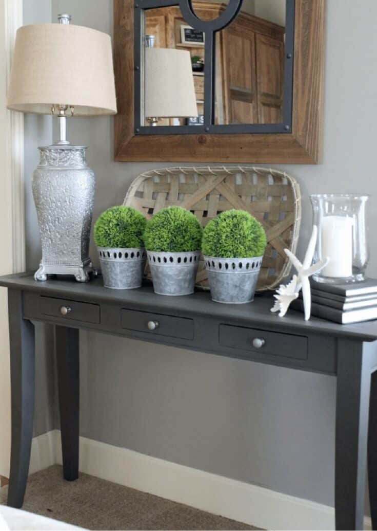 sofa table with silver lamp and other decor