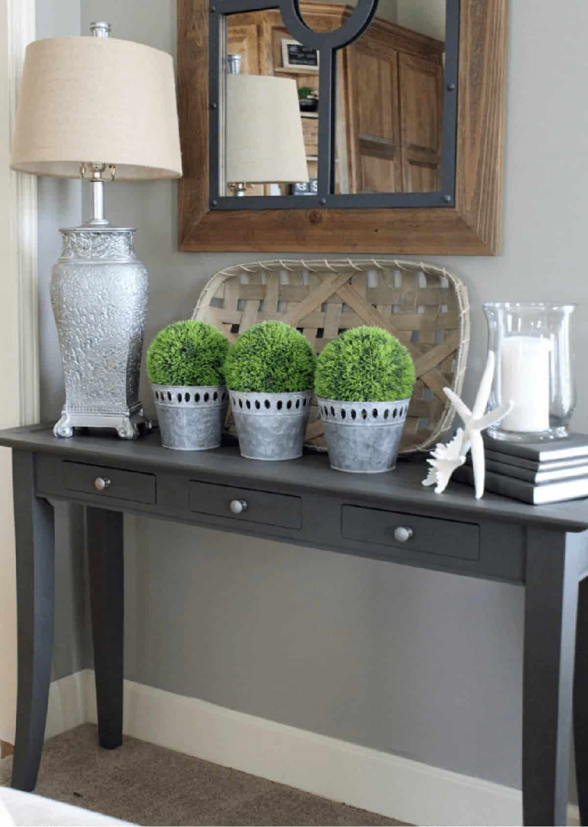 Gray sofa table with styled with silver decor accents.