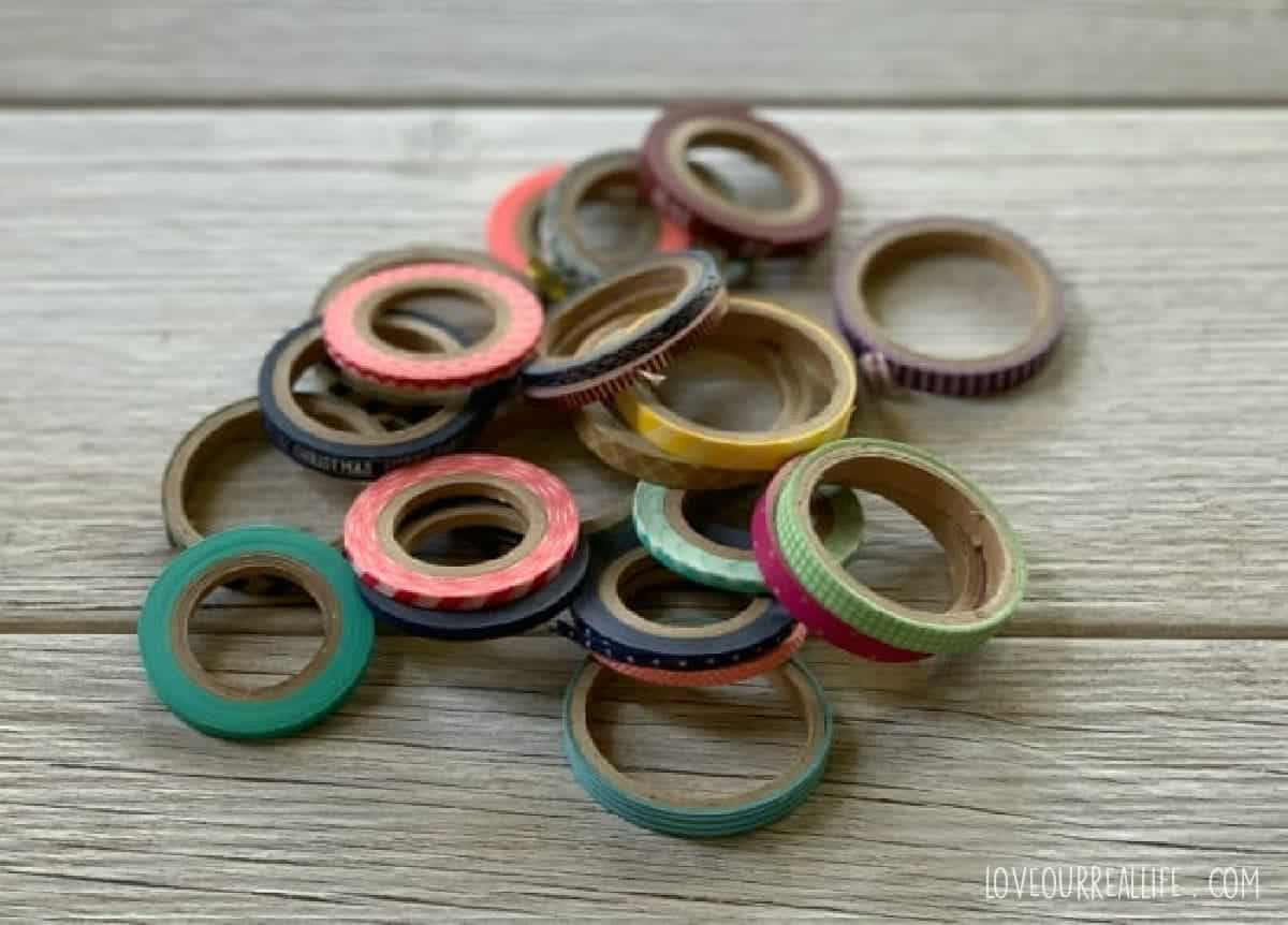 Multiple washi tape rolls in various colors on wooden table.
