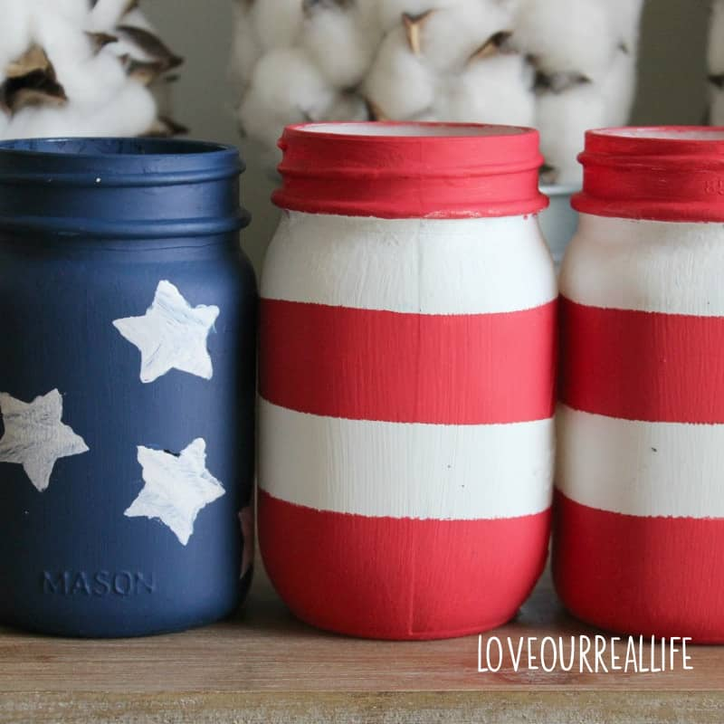 4th of July mason jars painted to look like the American flag for July decor.