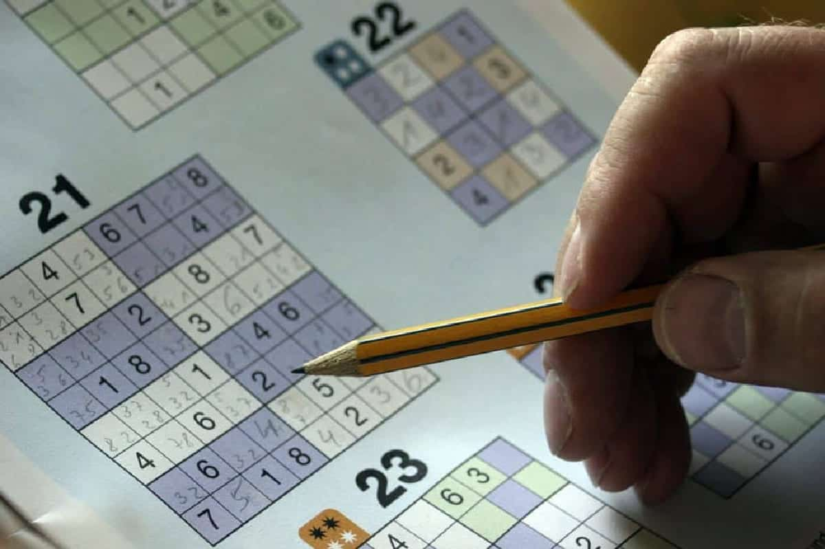 Person's hand holding pencil, solving sudoku puzzle.