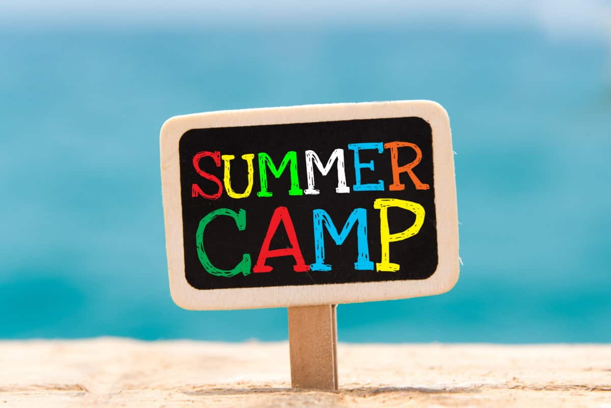"""Colorful sign in sand that reads """"summer camp""""."""