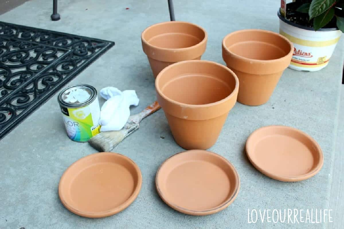 Three terracotta pots with saucers, white paint, a sock, and paint brush on front porch.