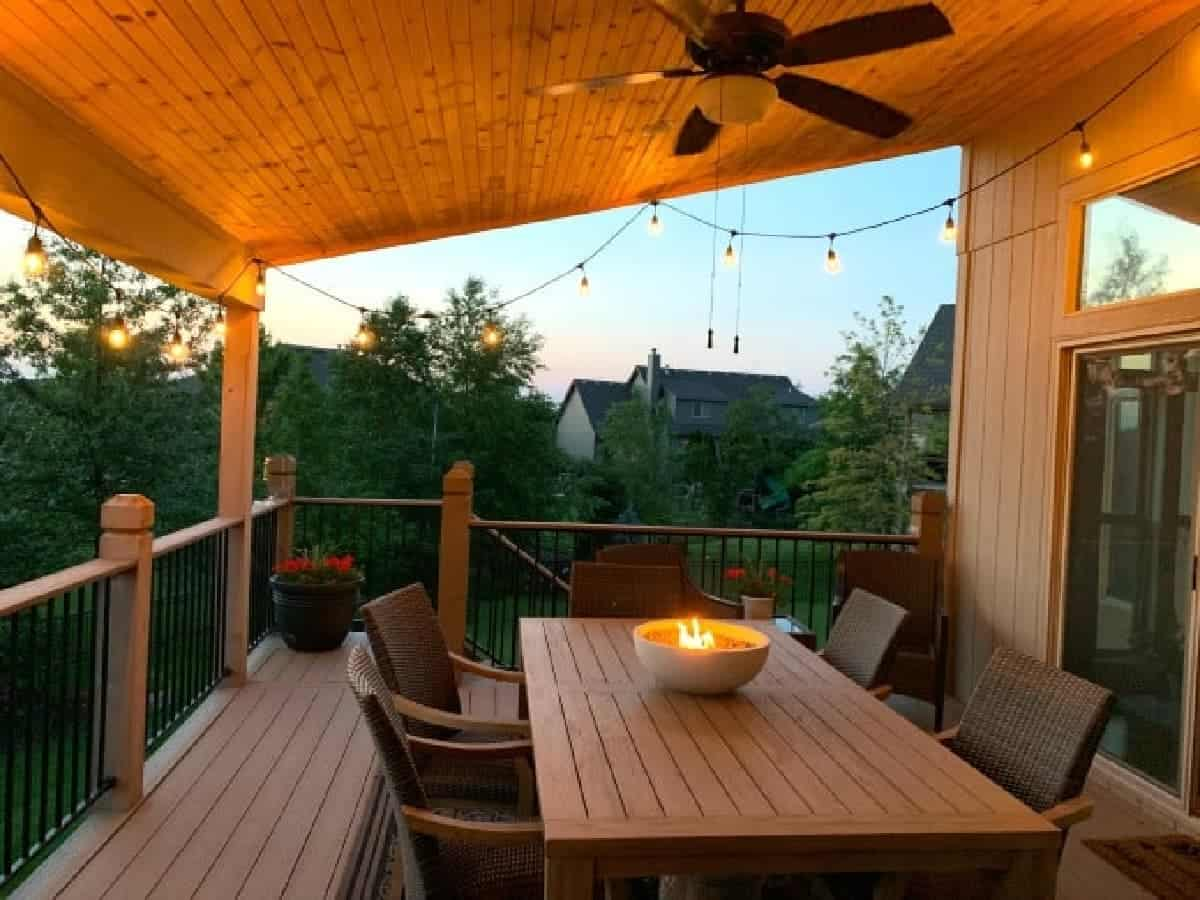 Dusk view of covered deck with string lights and a tabletop fire bowl on teak table.
