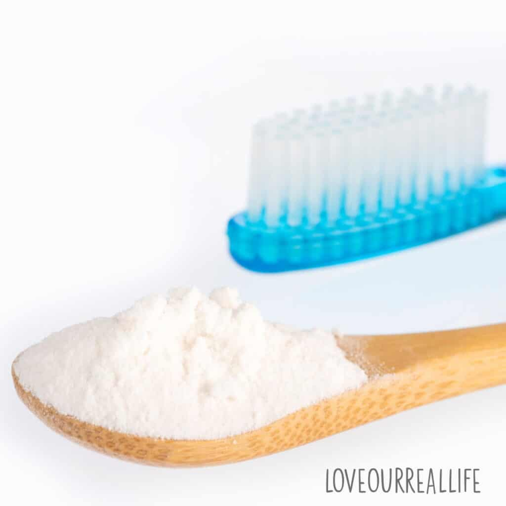 White background with wooden spoon filled with baking soda and blue toothbrush.