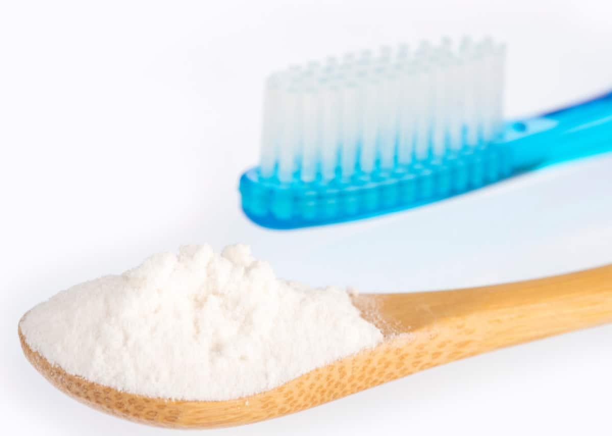 Spoon full of baking soda beside aqua blue toothbrush with white background.