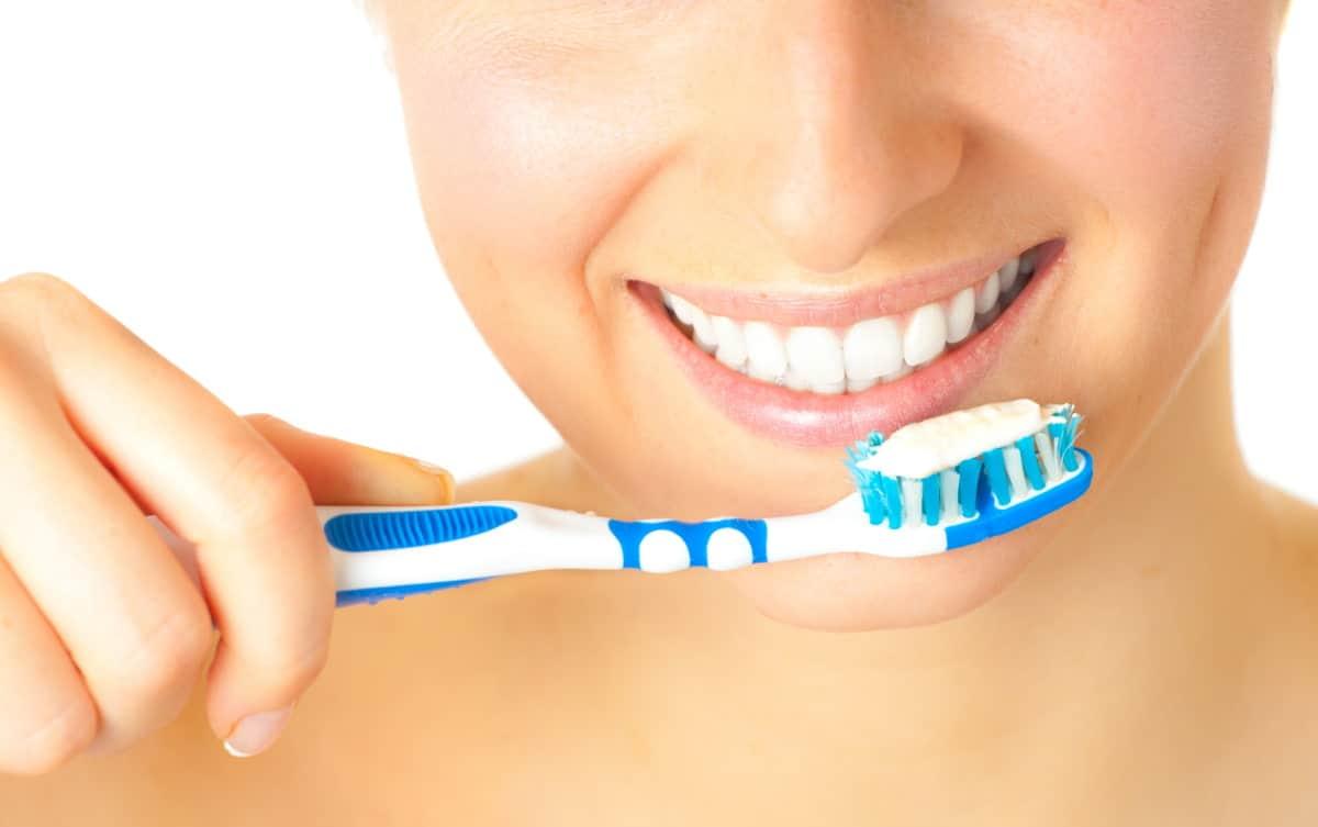 Close up of woman preparing to brush her teeth.
